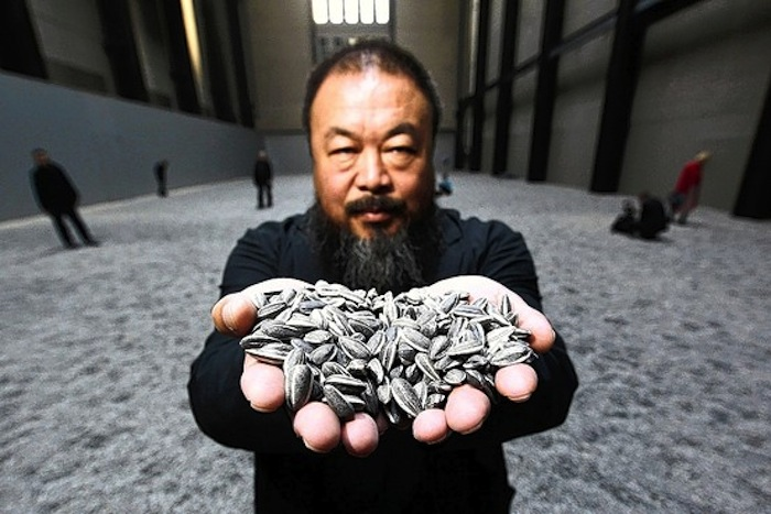 Ai Weiwei with some seeds from his mammoth installation 'Sunflower Seeds'.