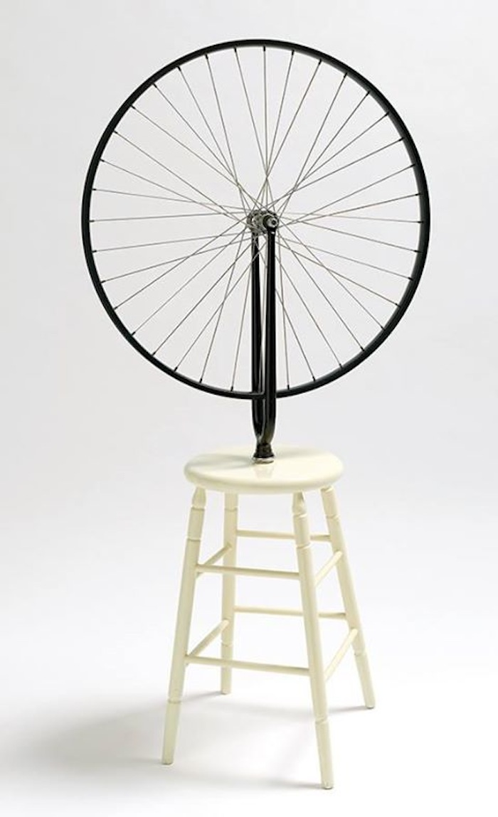 """If contemporary art were a religion – and maybe it is – its symbol might be an upside-down bicycle wheel mounted on a wooden stool. As a sign it stands for transubstantiation just as surely as a wafer placed in the mouths of the faithful. It promises that ordinary objects can be magically transformed by their placement – literally and figuratively – as art. Marcel Duchamp created Bicycle wheel one hundred years ago. The committee rejected it because it was ""not art"". And this is the readymade's most radical gesture: to shift the art conversation from the question ""is it beautiful?"" to one that asks, ""is it art?"" It moves art from the aesthetic to the conceptual, or, in Duchamp's own words, from ""the retinal"" to an art of the mind. The slippery legacy of the readymade is explored in Reinventing the Wheel: The Readymade Century, coming to Monash University Museum of Art in October."